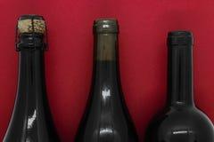 Κλειστός με βουλώνει τα μαύρα μπουκάλια σαμπάνιας και κρασιού στο κόκκινο υπόβαθρο στοκ φωτογραφίες με δικαίωμα ελεύθερης χρήσης