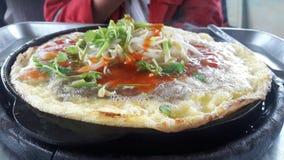 Κλειστό επάνω στρείδι πυρκαγιάς με το αυγό στο καυτό πιάτο στοκ εικόνες