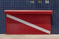 Κλειστό παραθυρόφυλλο καταστημάτων που χρωματίζεται στην κόκκινη σημαία κατάδυσης σκαφάνδρων με ένα wal στοκ φωτογραφία