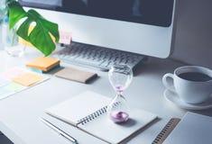 κλεψύδρα με το worktable γραφείο Χρόνος, έννοια κινήτρου Στοκ Φωτογραφία