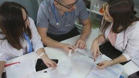 Κλινική γραφείων γιατρών συνεδρίασης για τον πίνακα Γιατρός ανδρών και δύο γιατροί γυναικών εργάζονται με τα έγγραφα φιλμ μικρού μήκους