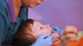 Κλινική ιατρικής Ένα μωρό με την εγκεφαλική ασθένεια παράλυσης Μια γυναίκα τελειώνει το μασάζ λεκτικής θεραπείας απόθεμα βίντεο