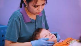 Κλινική ιατρικής Ένα μωρό με την εγκεφαλική ασθένεια παράλυσης που λαμβάνει ένα χαλαρώνοντας μασάζ προσώπου μυών απόθεμα βίντεο