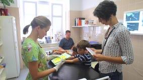 Κλινική κτηνιάτρων Ένας νέος ιδιοκτήτης γυναικών της γάτας, περνά τα έγγραφα στη νοσοκόμα στα άσπρα γάντια Τα αγόρια 4-8 παιδιών  απόθεμα βίντεο