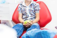 κλινική οδοντική Υποδοχή, εξέταση του ασθενή Προσοχή δοντιών Μικρό παιδί που κρατά ένα μήλο καθμένος σε έναν οδοντικό στοκ εικόνα