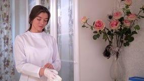 Κλινική ομορφιάς Ένας νέος γιατρός προετοιμάζεται για τη διαδικασία, φορώντας τα γάντια 4K η αργή Mo απόθεμα βίντεο