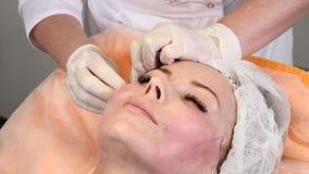 Κλινική ομορφιάς Ο νέος θηλυκός πελάτης παίρνει την ανύψωση προσώπου νημάτων Cosmetologist στα γάντια που κάνει το πρόσωπο αντι-γ απόθεμα βίντεο