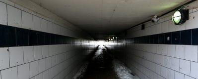 Κοίταγμα κάτω από μια υπόγεια σήραγγα με το φως στο τέλος γραπτό στοκ φωτογραφία με δικαίωμα ελεύθερης χρήσης