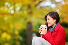 Κοίταγμα καφέ κατανάλωσης γυναικών φθινοπώρου/πτώσης Στοκ Εικόνες