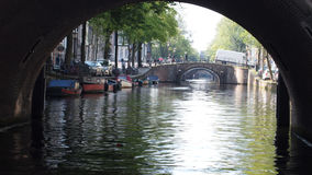 Κοίταγμα μέσω μιας γέφυρας αψίδων σε ένα ολλανδικό κανάλι με τις βάρκες και το νερό στοκ εικόνα με δικαίωμα ελεύθερης χρήσης