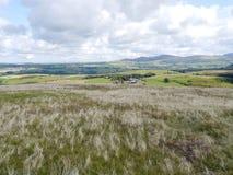 Κοίταγμα στους απόμακρους λόφους από το χλοώδες οροπέδιο με το αγρόκτ στοκ εικόνες