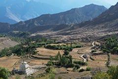 Κοιλάδα βουνών: τομείς στα πεζούλια που κατεβαίνουν από τις κλίσεις, πράσινα δέντρα, άσπρο βουδιστικό stupa στον πρόσθιο, υψηλό β Στοκ εικόνες με δικαίωμα ελεύθερης χρήσης