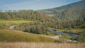 Κοιλάδα με έναν ποταμό και μια εθνική οδός στα πράσινα βουνά Στοκ Φωτογραφίες