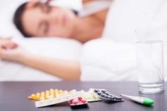 Κοιμισμένα ανθυγειινά γυναίκα και χάπια στο nightstand Στοκ Εικόνες