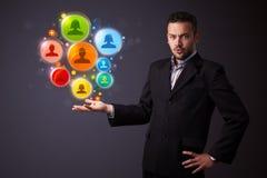 Κοινωνικά εικονίδια δικτύων στο χέρι ενός επιχειρηματία Στοκ Εικόνα