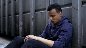 Κοινωνικά προβλήματα, άστεγο αγόρι αφροαμερικάνων που αισθάνονται τη μοναξιά, μάταιος τύπος στοκ φωτογραφία με δικαίωμα ελεύθερης χρήσης