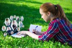 Κοινωνική έννοια δικτύων - έφηβη που βρίσκεται σε πράσινο στο πάρκο και Στοκ Εικόνα