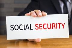 Κοινωνική ασφάλιση, μήνυμα στην άσπρη κάρτα και λαβή κοντά στοκ εικόνα