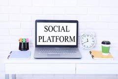 Κοινωνική πλατφόρμα Λέξεις στην οθόνη Εργασιακός χώρος με τον υπολογιστή, το φλιτζάνι του καφέ και το σημειωματάριο Μοντέρνο διάσ Στοκ Εικόνα