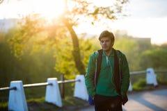 Κοινός νεαρός άνδρας που περπατά στην πόλη που ακούει στη μουσική με τα ακουστικά -αυτιών στο ηλιοβασίλεμα Θέμα μουσικής στο σχέδ στοκ εικόνες