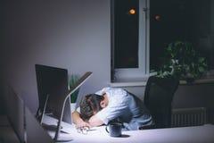 Κοισμένος νεαρός άνδρας που εργάζεται στον υπολογιστή τη νύχτα στο σκοτεινό γραφείο Στοκ Εικόνες