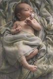 Κοισμένος νεογέννητο μωρό που βάζει στο κρεβάτι που τυλίγεται στο μαντίλι Στοκ Εικόνα