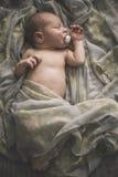 Κοισμένος νεογέννητο μωρό που βάζει στο κρεβάτι που τυλίγεται στο μαντίλι Στοκ εικόνες με δικαίωμα ελεύθερης χρήσης