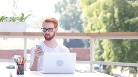 Κοιτάζοντας βιαστικά σε Smartphone καθμένος στο υπαίθριο γραφείο, κόκκινες τρίχες Στοκ Εικόνα