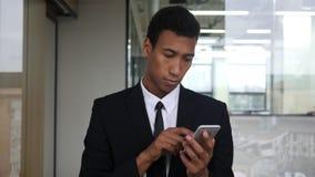 Κοιτάζοντας βιαστικά σε Smartphone, μαύρος επιχειρηματίας στην αρχή Στοκ φωτογραφία με δικαίωμα ελεύθερης χρήσης