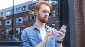 Κοιτάζοντας βιαστικά σε Smartphone, που στέκεται έξω από το κτίριο γραφείων Στοκ Εικόνες
