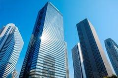 Κοιτάζοντας επάνω στην άποψη στην οικονομική περιοχή, οι σκιαγραφίες της πόλης ουρανοξυστών απεικονίζουν το μπλε ουρανό, φω'τα ήλ Στοκ Φωτογραφία