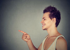 Κοιτάξτε εκεί! Ευτυχής νεαρός άνδρας που δείχνει με το δάχτυλο σε κάποιο Στοκ Εικόνα