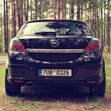 Κοιτάξτε επίμονα Splavy, Τσεχία - 19 Αυγούστου 2017: μαύρη στάση Opel Astra Χ αυτοκινήτων από το δρόμο ασφάλτου μεταξύ των δασών  Στοκ Φωτογραφία