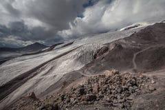 Κοιλάδα βουνών χιονιού με τις πέτρες, δύσκολες κλίσεις, μπλε ουρανός Στοκ Εικόνες