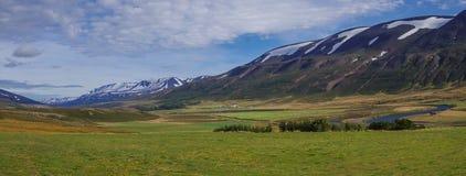 Κοιλάδα πανοράματος των χιονισμένων βουνών Όμορφο θερινό έδαφος Στοκ Φωτογραφία
