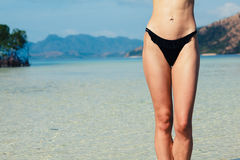 Κοιλιά και πόδια της γυναίκας που στέκονται στην τροπική παραλία Στοκ Εικόνα