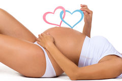 Κοιλιά κινηματογραφήσεων σε πρώτο πλάνο της εγκύου γυναίκας Γένος: αγόρι, κορίτσι ή δίδυμα; Δύο καρδιές στοκ εικόνα με δικαίωμα ελεύθερης χρήσης