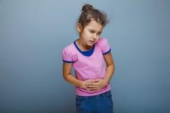 Κοιλιακός πόνος παιδιών κοριτσιών σε ένα γκρίζο υπόβαθρο στοκ φωτογραφία με δικαίωμα ελεύθερης χρήσης