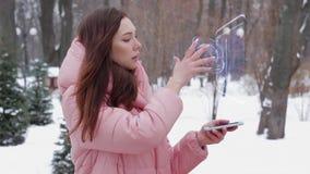 Κοκκινομάλλες κορίτσι με το σύγχρονο smartphone ολογραμμάτων φιλμ μικρού μήκους