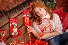 Κοκκινομάλλες κορίτσι σε ένα άσπρο πουλόβερ και τζιν σε ένα υπόβαθρο των διακοσμήσεων και των καραμελών Χριστουγέννων Στοκ Εικόνες