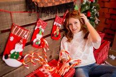 Κοκκινομάλλες κορίτσι σε ένα άσπρο πουλόβερ και τζιν σε ένα υπόβαθρο των διακοσμήσεων και των καραμελών Χριστουγέννων Στοκ Εικόνα