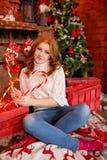 Κοκκινομάλλες κορίτσι σε ένα άσπρο πουλόβερ και τζιν σε ένα υπόβαθρο των διακοσμήσεων και των καραμελών Χριστουγέννων Στοκ εικόνα με δικαίωμα ελεύθερης χρήσης