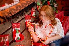 Κοκκινομάλλες κορίτσι σε ένα άσπρο πουλόβερ και τζιν σε ένα υπόβαθρο των διακοσμήσεων και των καραμελών Χριστουγέννων Στοκ φωτογραφία με δικαίωμα ελεύθερης χρήσης