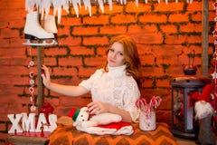Κοκκινομάλλες κορίτσι σε ένα υπόβαθρο των κόκκινων διακοσμήσεων Χριστουγέννων Στοκ Εικόνες