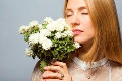 Κοκκινομάλλες κορίτσι στο στούντιο με μια άσπρη ανθοδέσμη των λουλουδιών Στοκ Φωτογραφία