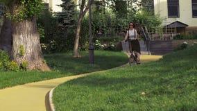 Κοκκινομάλλες οδηγώντας ποδήλατο γυναικών στην κεκλιμένη ράμπα στο πάρκο πόλεων απόθεμα βίντεο