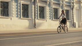 Κοκκινομάλλες οδηγώντας ποδήλατο γυναικών στο δρόμο πόλεων στο κτήριο υποβάθρου φιλμ μικρού μήκους