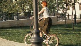 Κοκκινομάλλες οδηγώντας ποδήλατο γυναικών στο πάρκο πόλεων την ηλιόλουστη ημέρα απόθεμα βίντεο