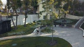 Κοκκινομάλλης γυναίκα που ανακυκλώνει ένα ποδήλατο στη στρωμένη πορεία στο θερινό πάρκο Πάρκο ποδηλάτων γυναικών φιλμ μικρού μήκους