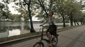 Κοκκινομάλλης γυναίκα που οδηγά ένα ποδήλατο στη λίμνη πόλεων υποβάθρου Πόλη ποδηλάτων γυναικών απόθεμα βίντεο